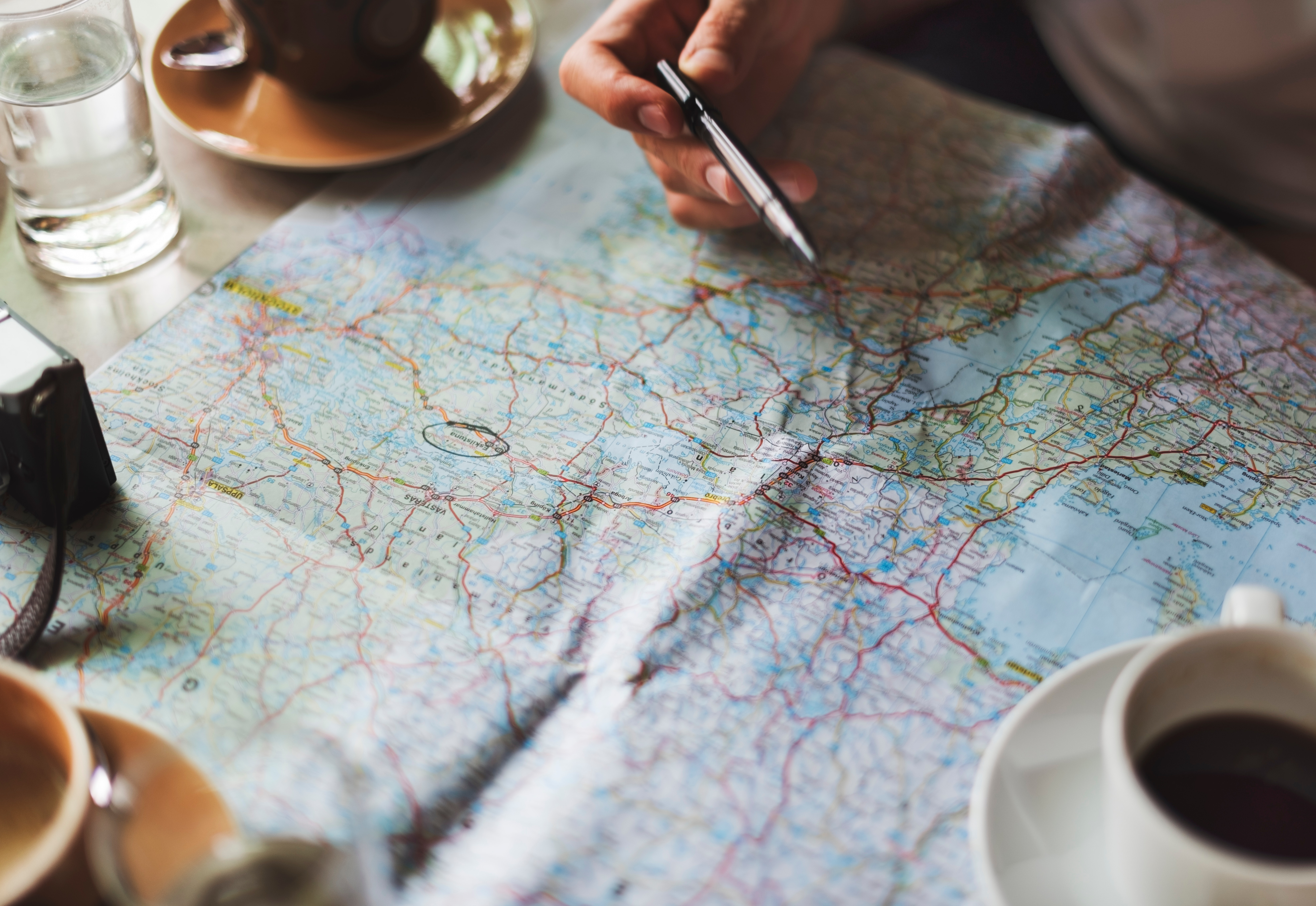 Map, coffee cup, pointing with pen at location, solo travel