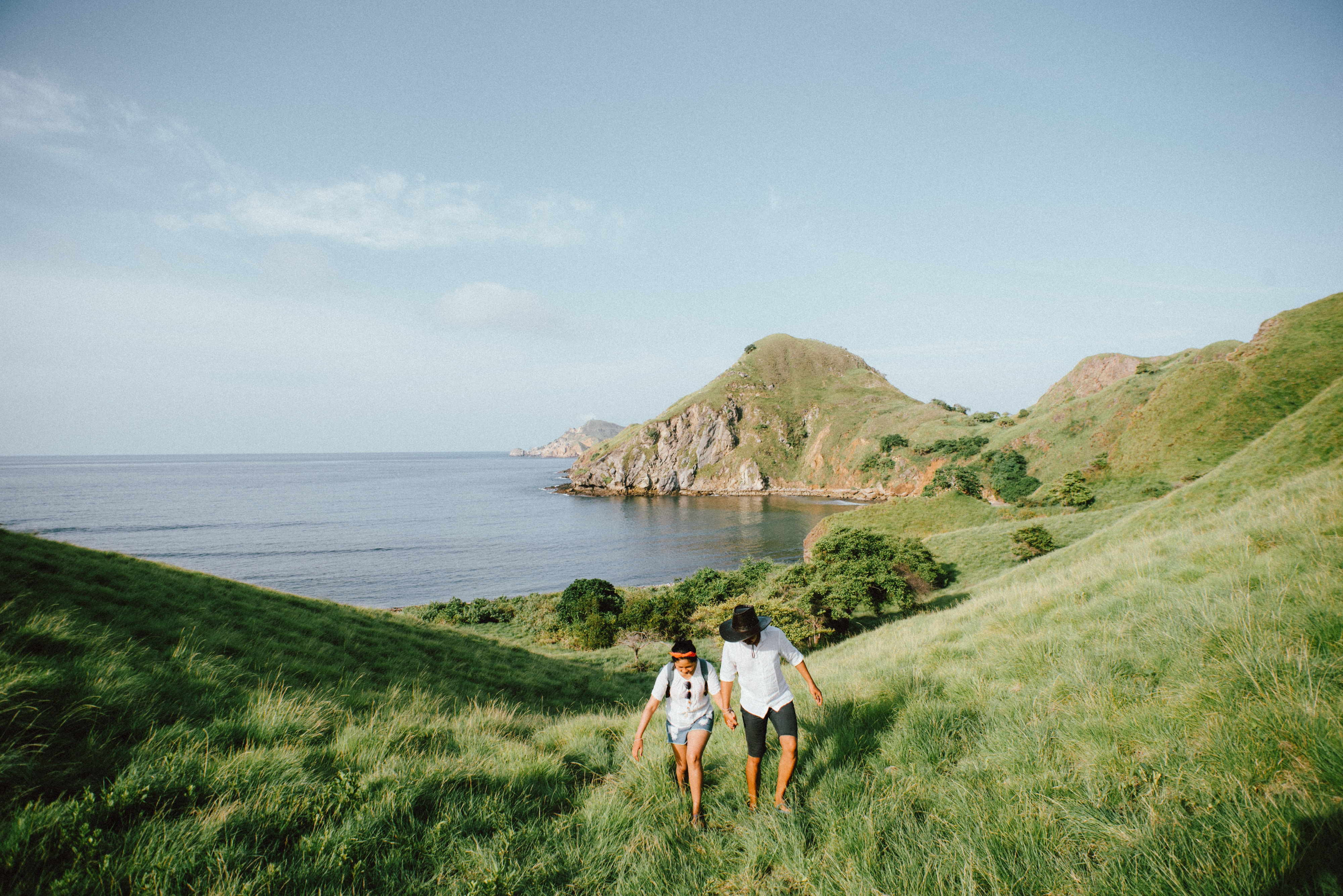 couple hiking up beautiful hill on the coast of an epic landscape