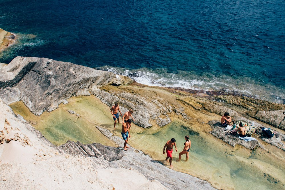 a group of friends in an amazing natural pool by the ocean