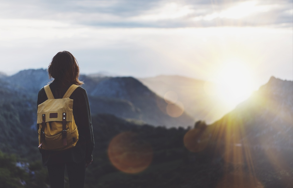 girl traveling solo looks out into the sunset as she hikes a mountain