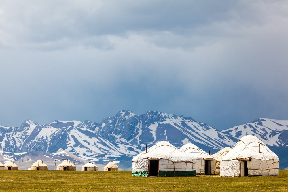 yurts on a field by the mountains in kyrgyzstan