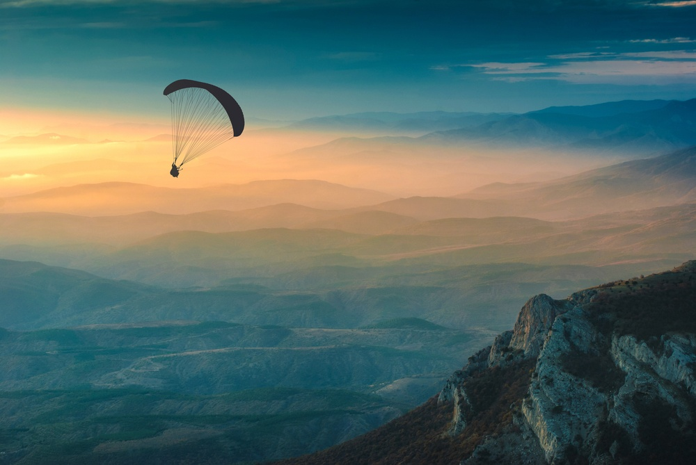 paraglider in the sunset sky overlooking an amazing landscape
